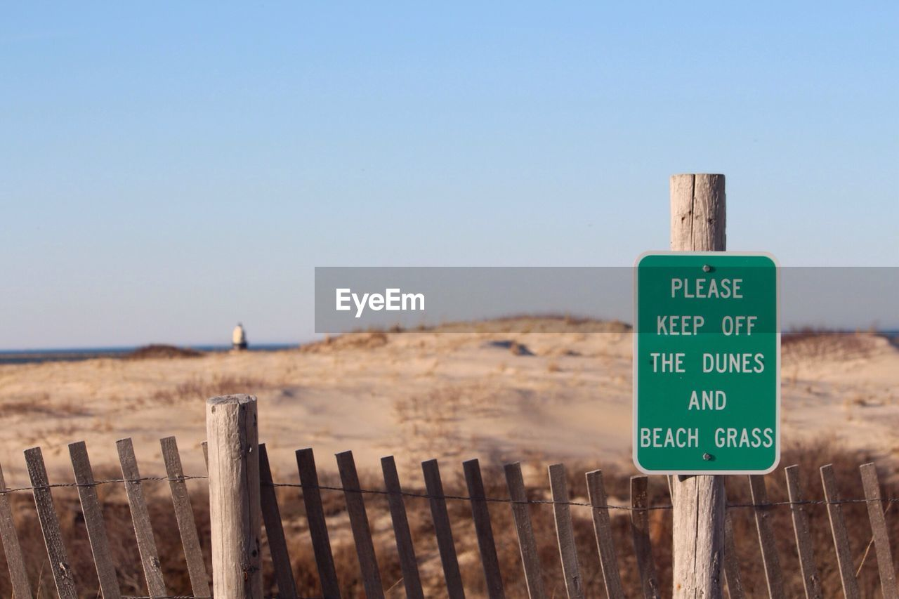 wood - material, clear sky, safety, beach, day, outdoors, text, protection, wooden post, nature, communication, tranquility, focus on foreground, sand, no people, green color, sea, scenics, beauty in nature, close-up, sky, animal themes