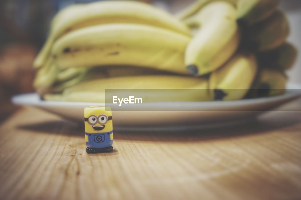 table, still life, indoors, close-up, banana, number, wellbeing, no people, healthy eating, food and drink, food, selective focus, wood - material, fruit, freshness, communication, plate, yellow, text, high angle view, temptation