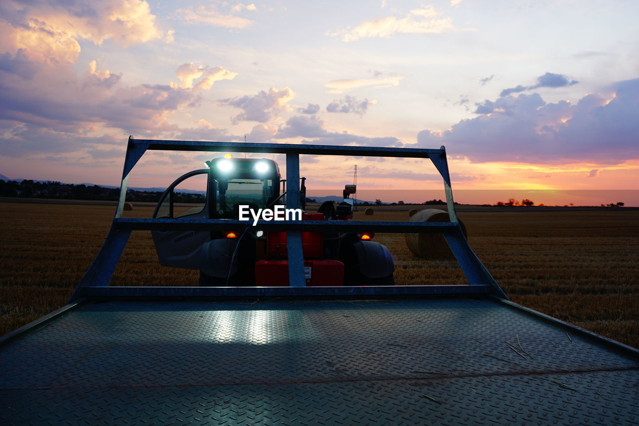 TRACTOR ON FIELD AGAINST SKY AT SUNSET
