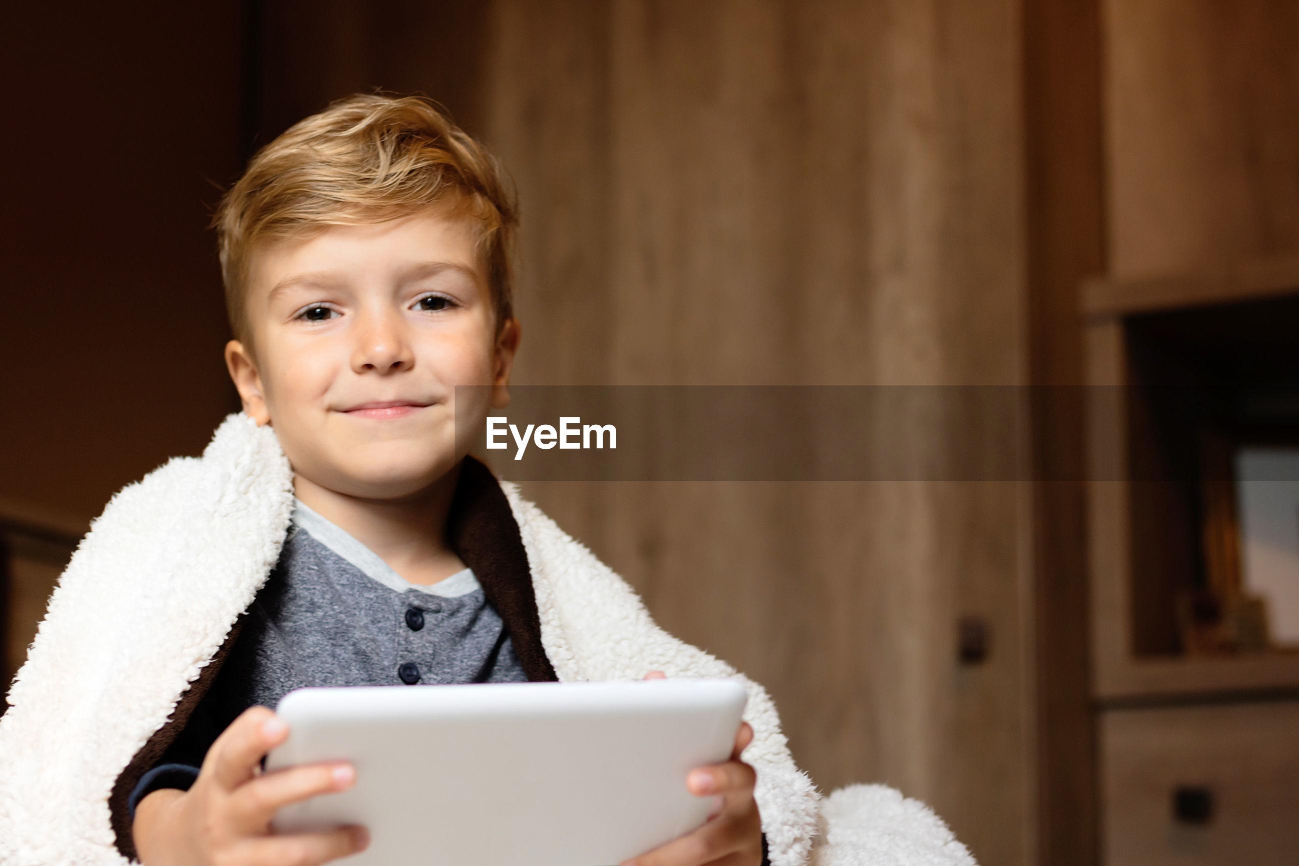 PORTRAIT OF SMILING BOY HOLDING SMART PHONE