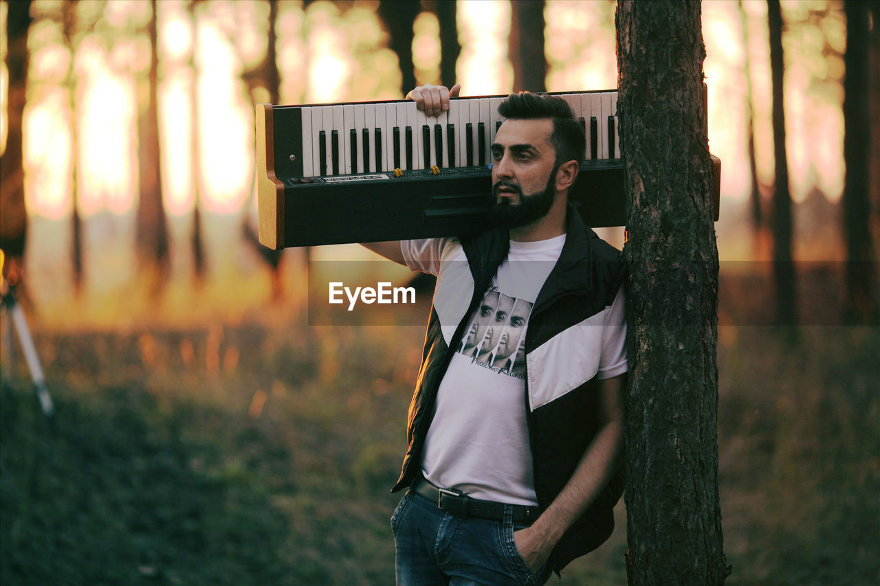Thoughtful man with keyboard instrument standing by trees in forest