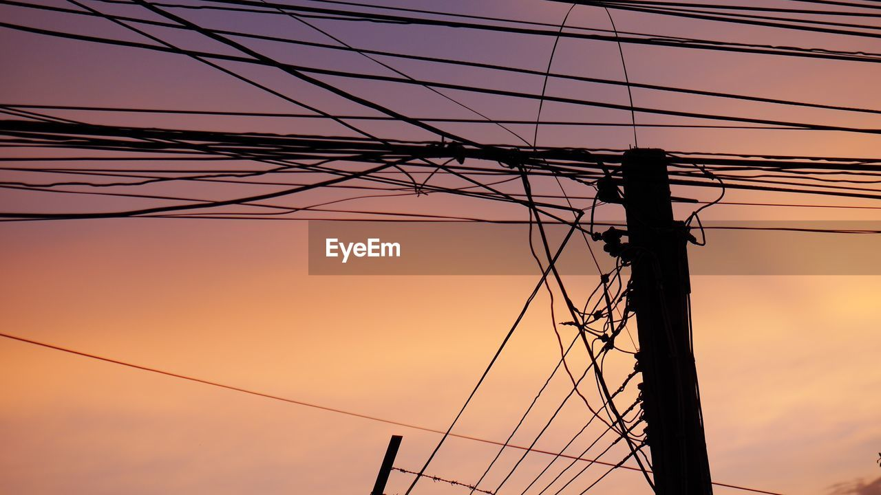 cable, electricity, power supply, power line, connection, technology, sunset, sky, fuel and power generation, electricity pylon, low angle view, no people, complexity, silhouette, pole, nature, orange color, outdoors, telephone line, telephone pole, electrical equipment, tangled, electrical component