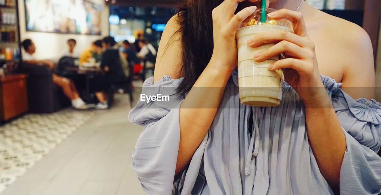Midsection of woman having drink while standing at cafe
