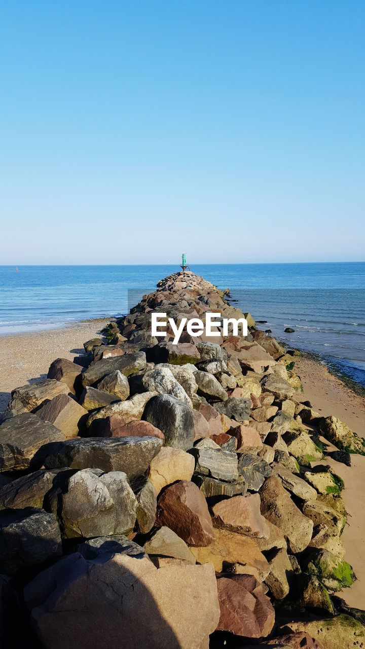 sea, horizon over water, water, nature, beach, clear sky, rock - object, scenics, tranquility, tranquil scene, beauty in nature, day, no people, sky, outdoors, groyne, pebble beach