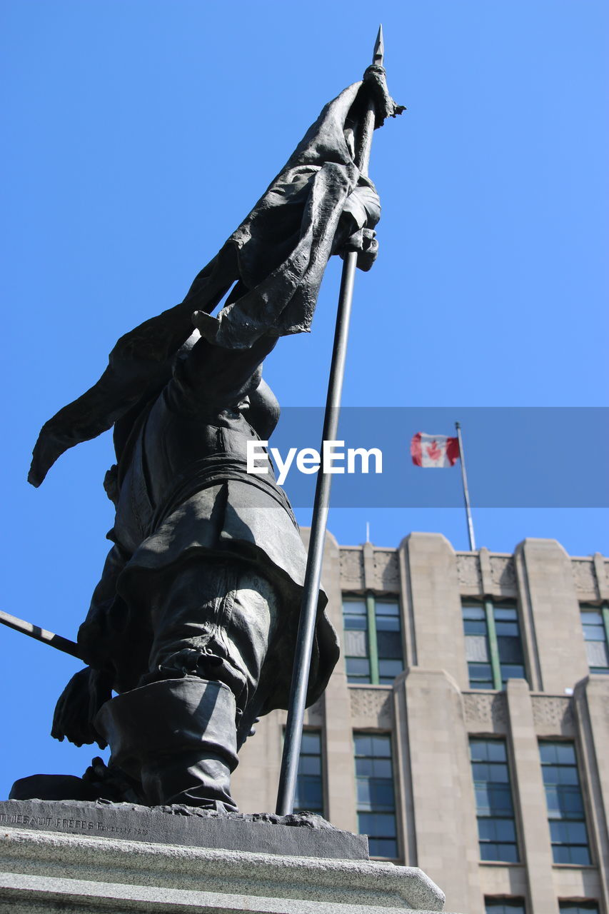 Low Angle View Of Statue And Building Against Blue Sky On Sunny Day