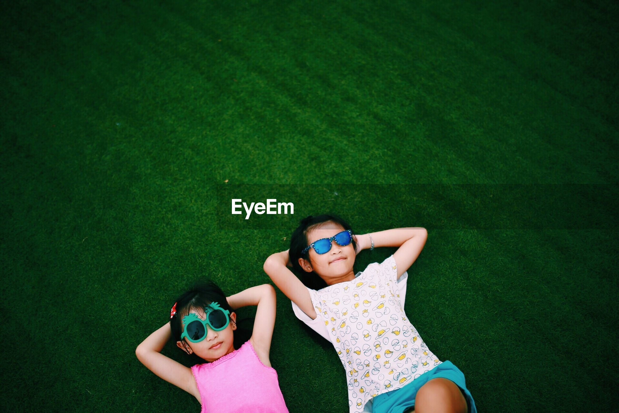 High angle view of friends wearing sunglasses lying on grassy field at park