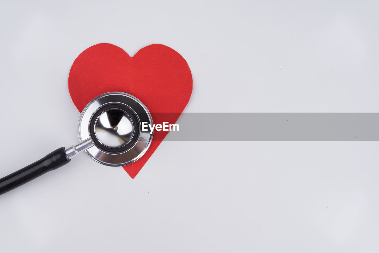 indoors, copy space, red, medical supplies, studio shot, white background, stethoscope, medical equipment, medical instrument, healthcare and medicine, still life, heart shape, no people, close-up, high angle view, love, positive emotion, emotion, single object, technology, pulse trace