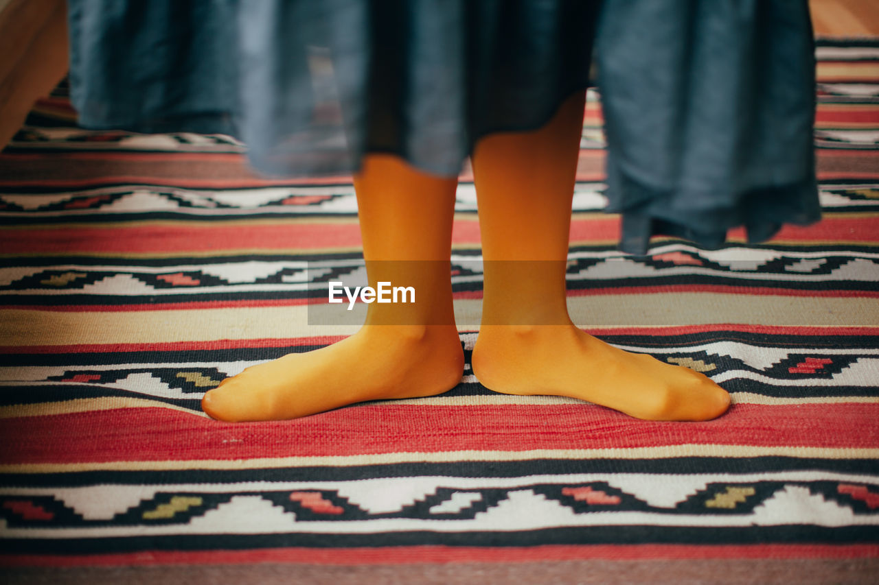Low Section Of Women Standing On Carpet