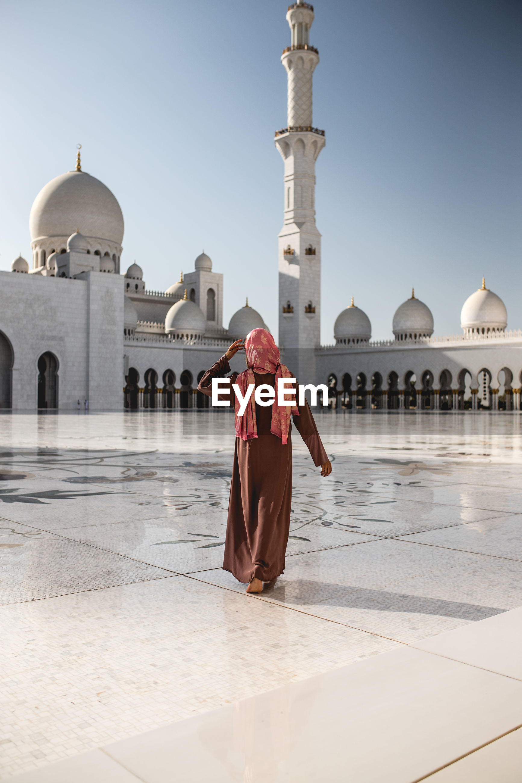Rear view of woman walking on floor against mosque