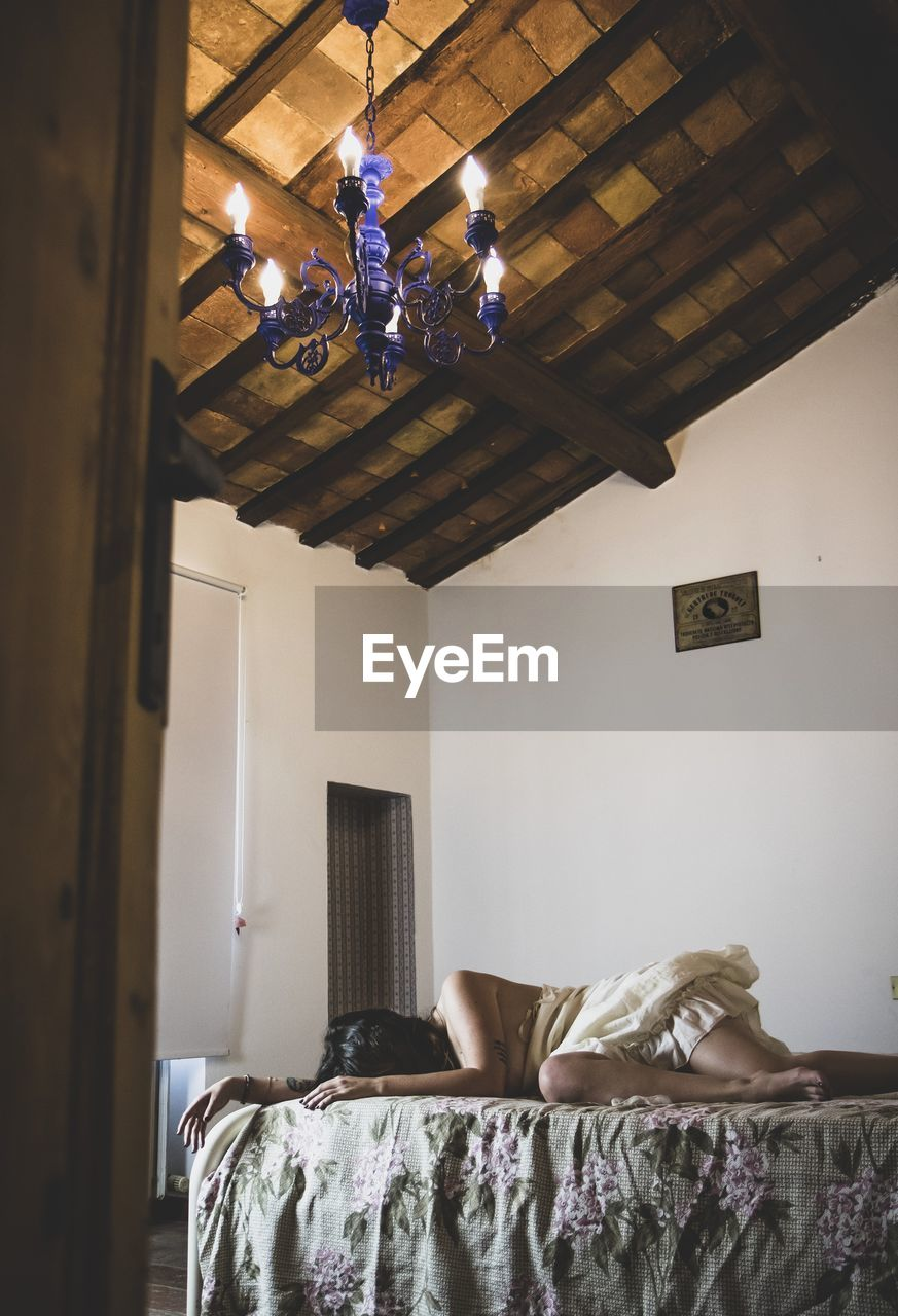 LOW ANGLE VIEW OF WOMAN RELAXING ON BED AGAINST CEILING