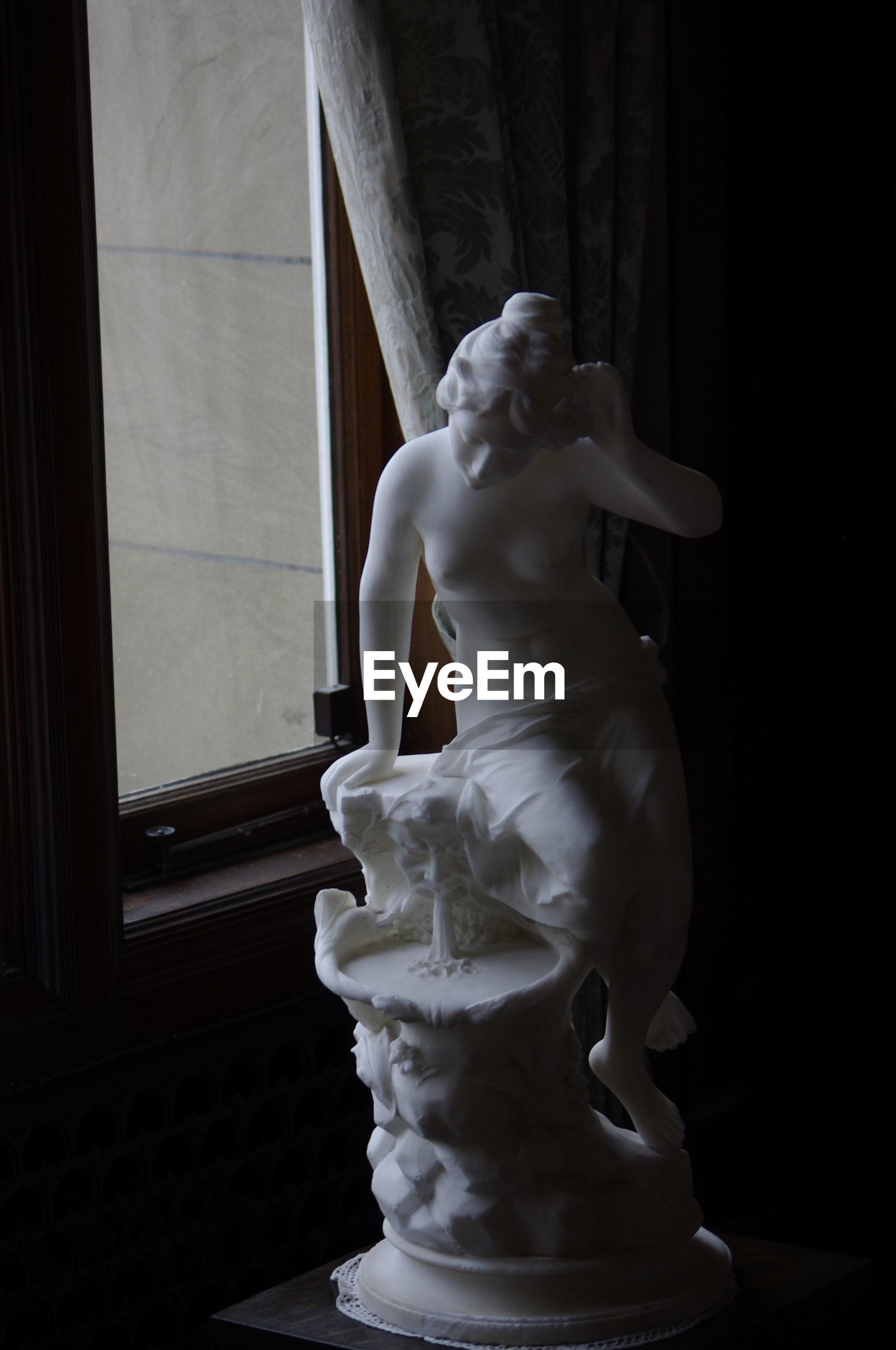 Statue by window in darkroom