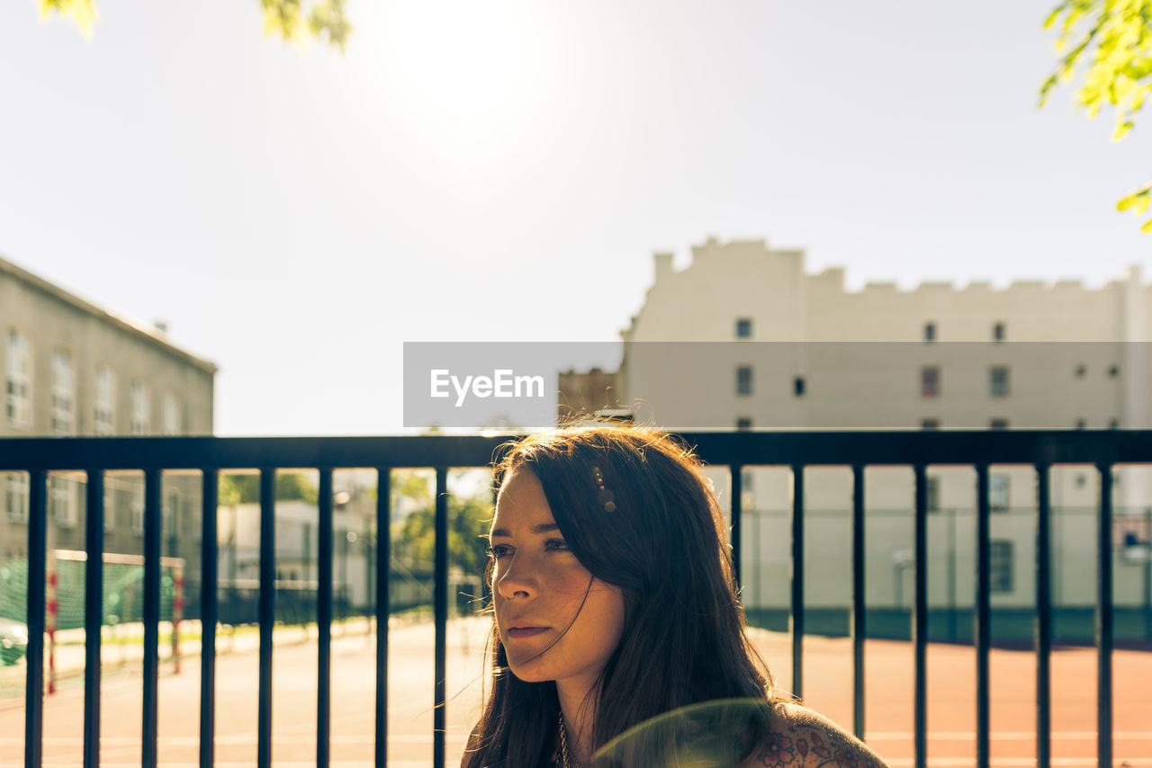 Close-up of young woman looking away against fence in city
