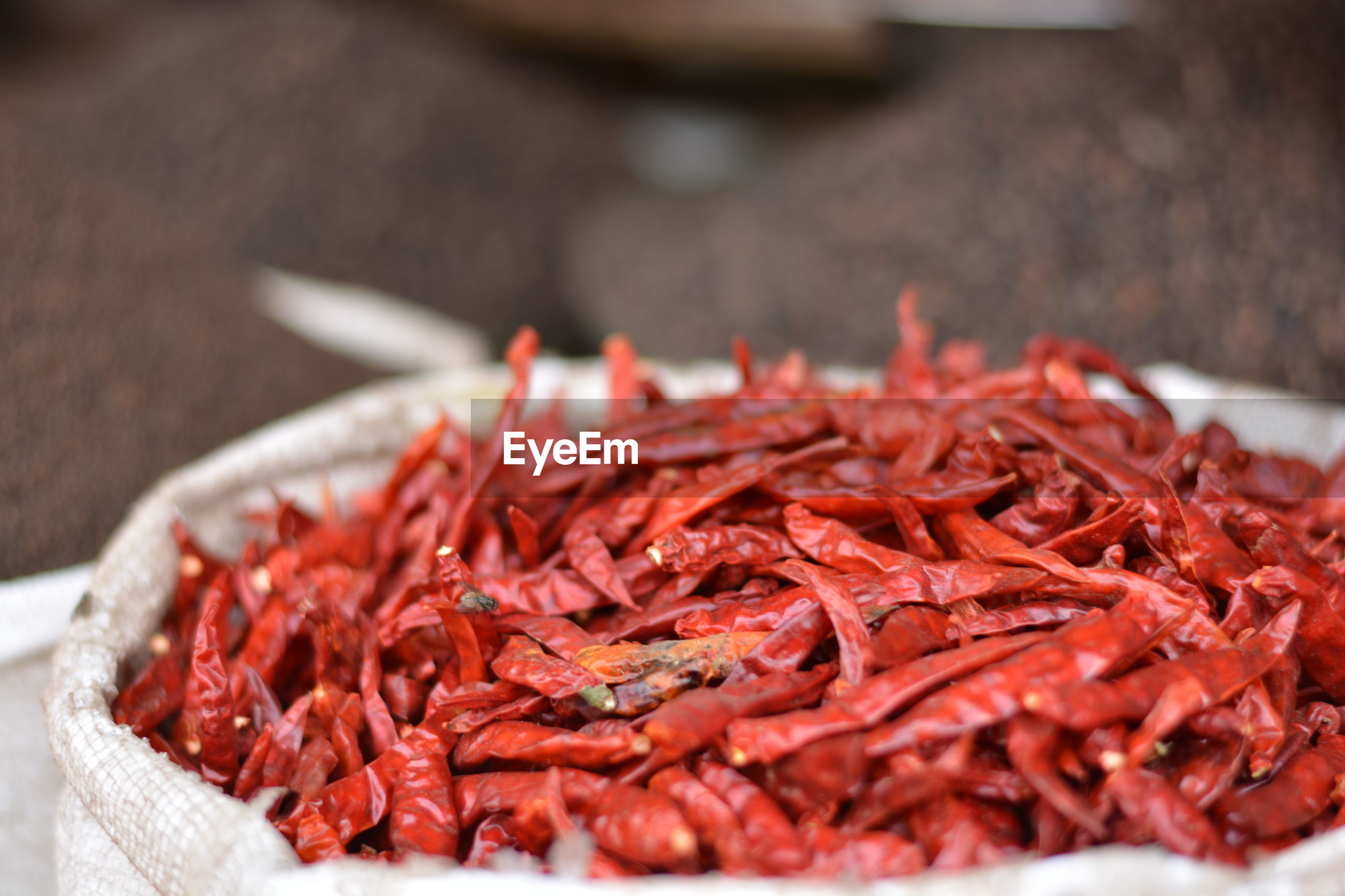 Close-up of dried red chili peppers in sack at market stall
