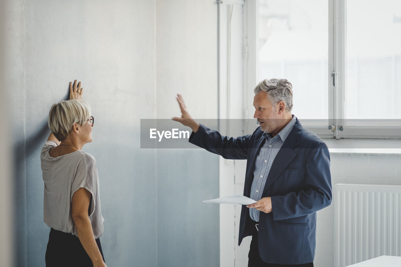 indoors, standing, adult, men, males, gesturing, three quarter length, real people, two people, business, business person, communication, waist up, people, businessman, senior adult, office, mature adult, looking, explaining