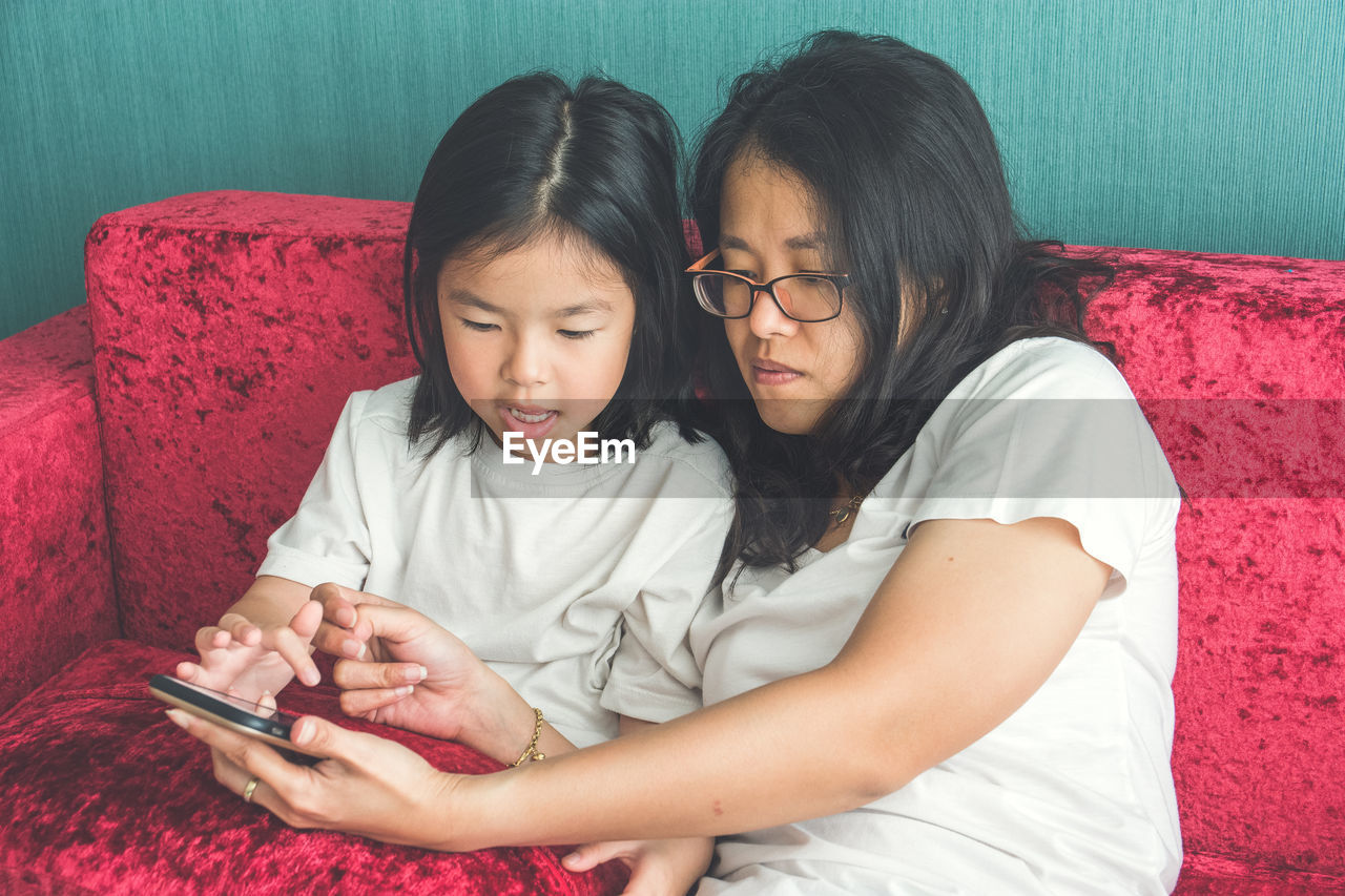 technology, wireless technology, two people, child, connection, togetherness, girls, childhood, family, women, furniture, females, bonding, indoors, lifestyles, real people, communication, looking, adult, casual clothing, hairstyle, hair, positive emotion