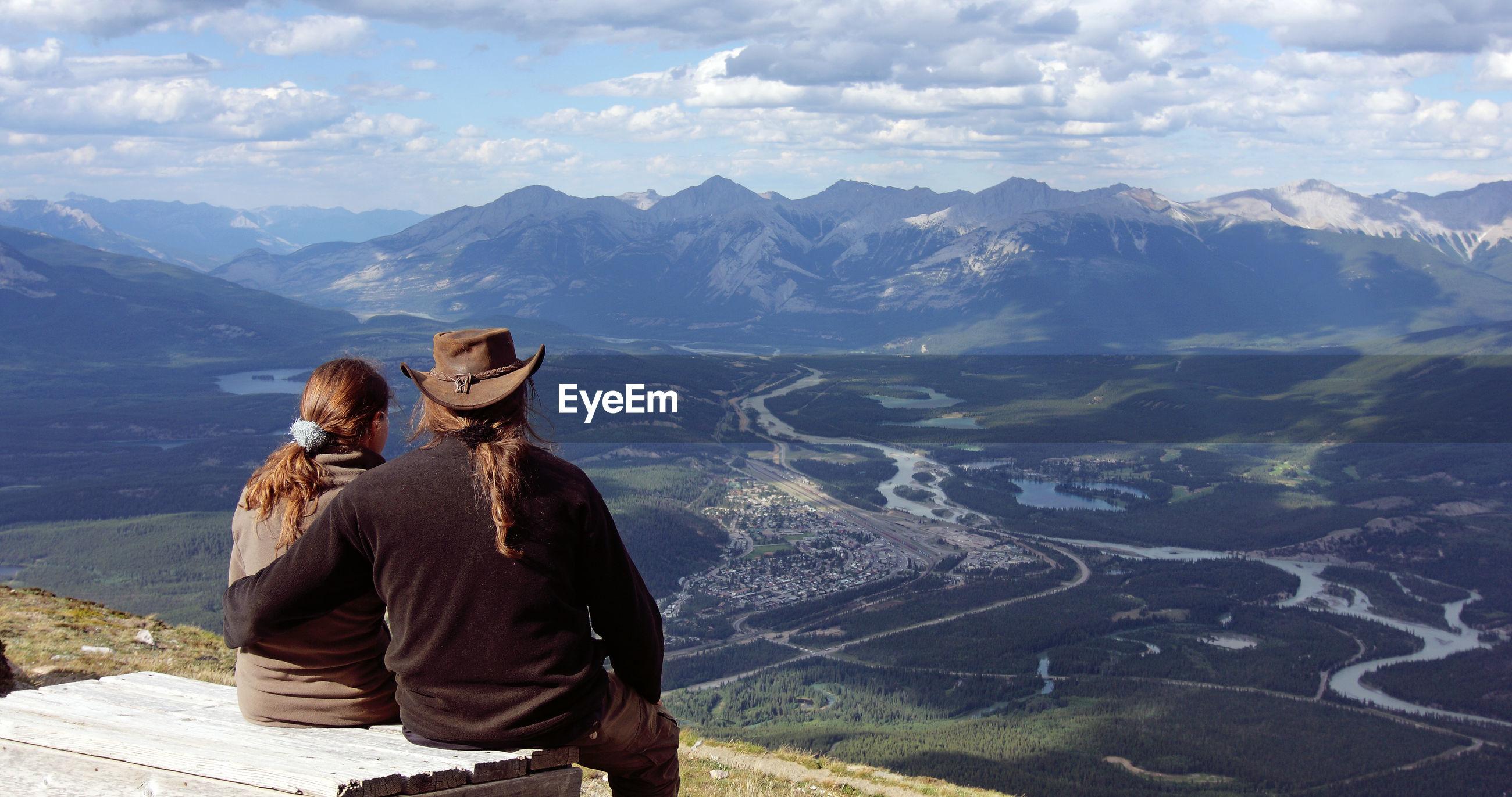 Couple overlooking landscape against sky