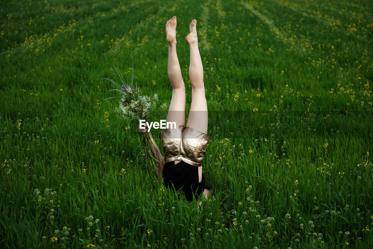 Woman doing headstand amidst plants on land