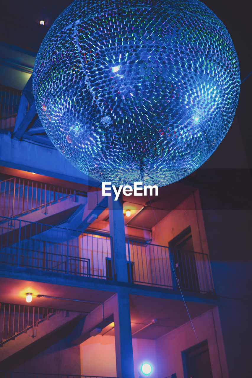 illuminated, night, low angle view, lighting equipment, no people, architecture, decoration, built structure, glowing, ceiling, hanging, sphere, indoors, nightclub, nightlife, disco ball, reflection, celebration, shiny, light, purple
