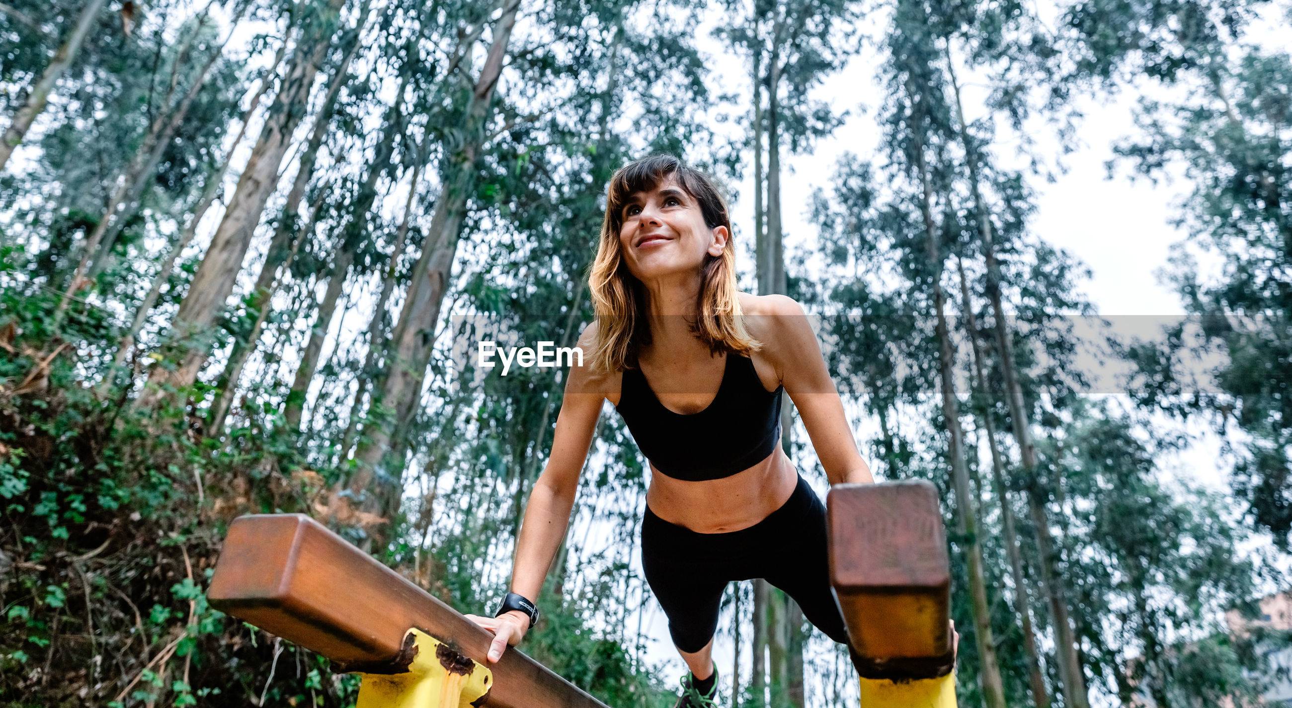 Low angle view of woman exercising against trees