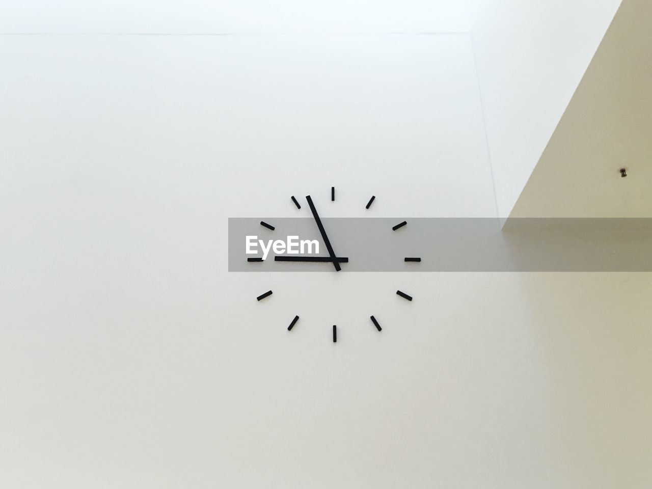 Low angle view of clock on white wall