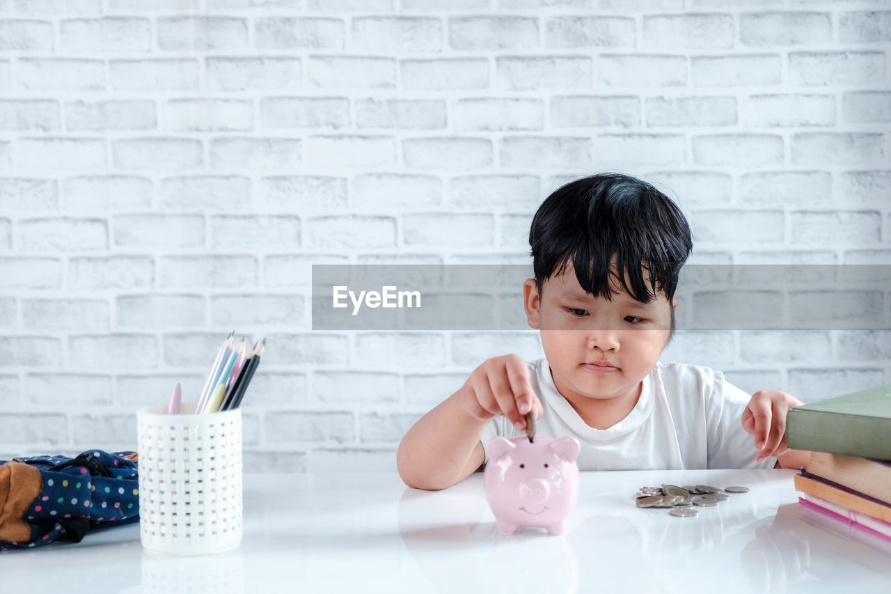childhood, portrait, table, piggy bank, child, indoors, savings, front view, headshot, coin, one person, investment, holding, males, finance, business, offspring, men, wealth, brick, responsibility, innocence, counting, inserting