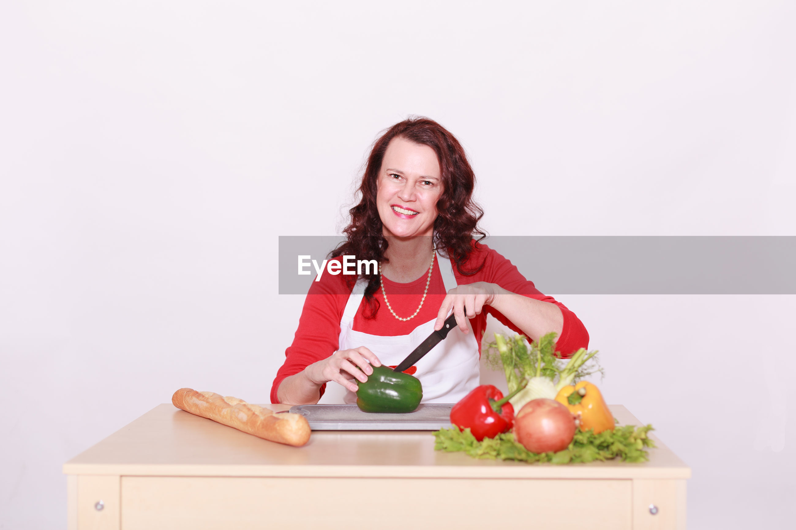 Portrait of smiling woman cutting food while sitting at table against white background