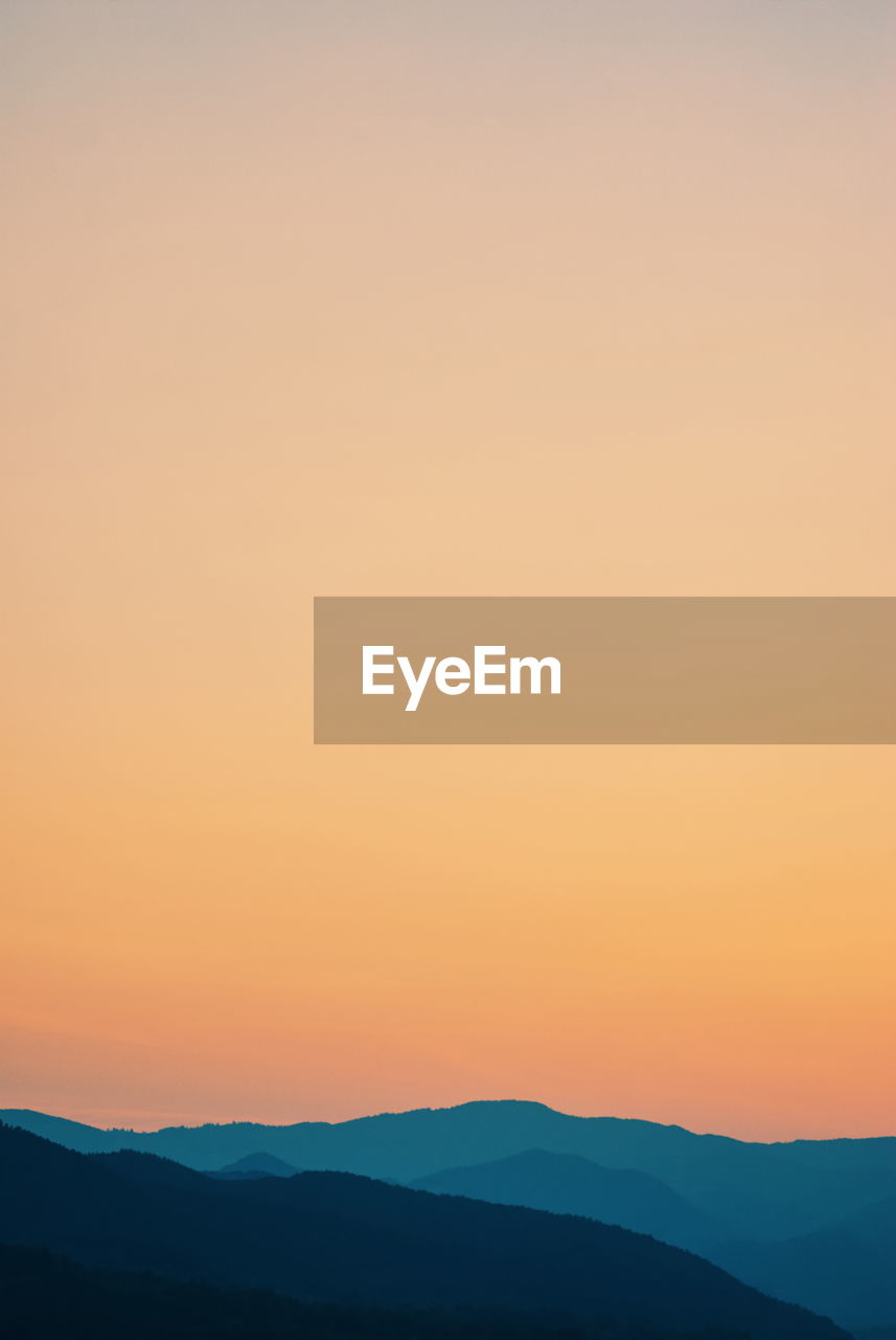 Scenic view of silhouette mountain against orange sky during sunset