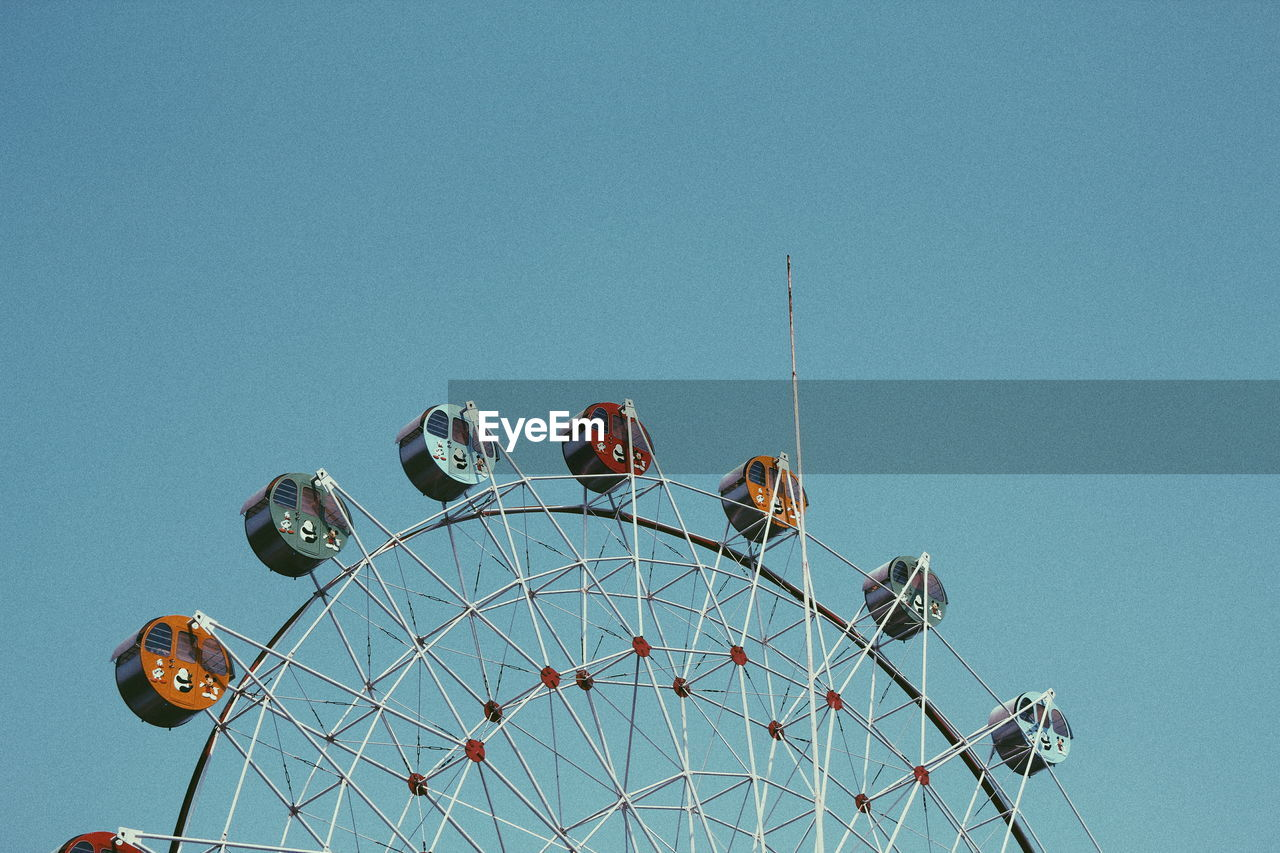 amusement park, arts culture and entertainment, clear sky, low angle view, amusement park ride, ferris wheel, copy space, leisure activity, blue, no people, day, outdoors, big wheel, sky