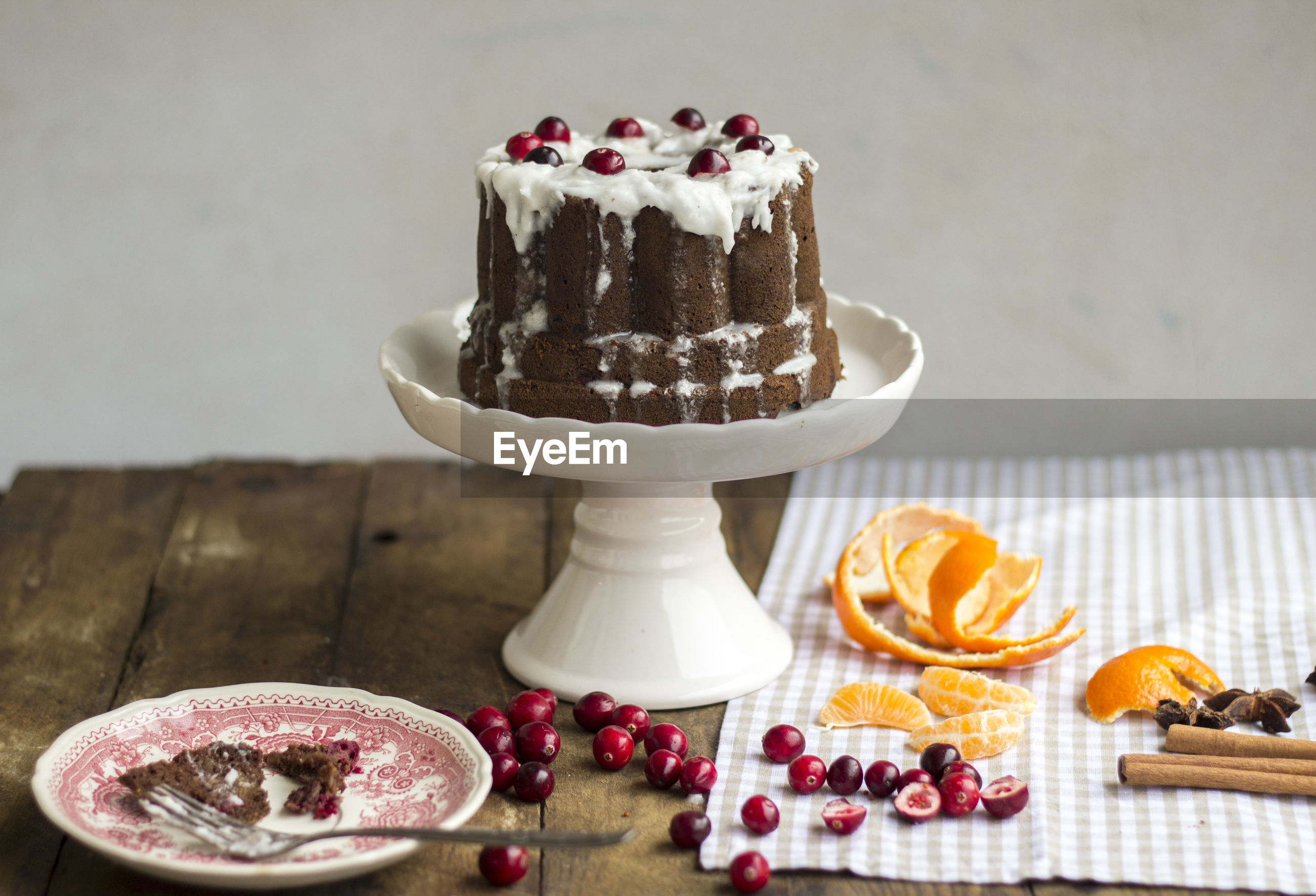 Cake with cranberries on stand over table