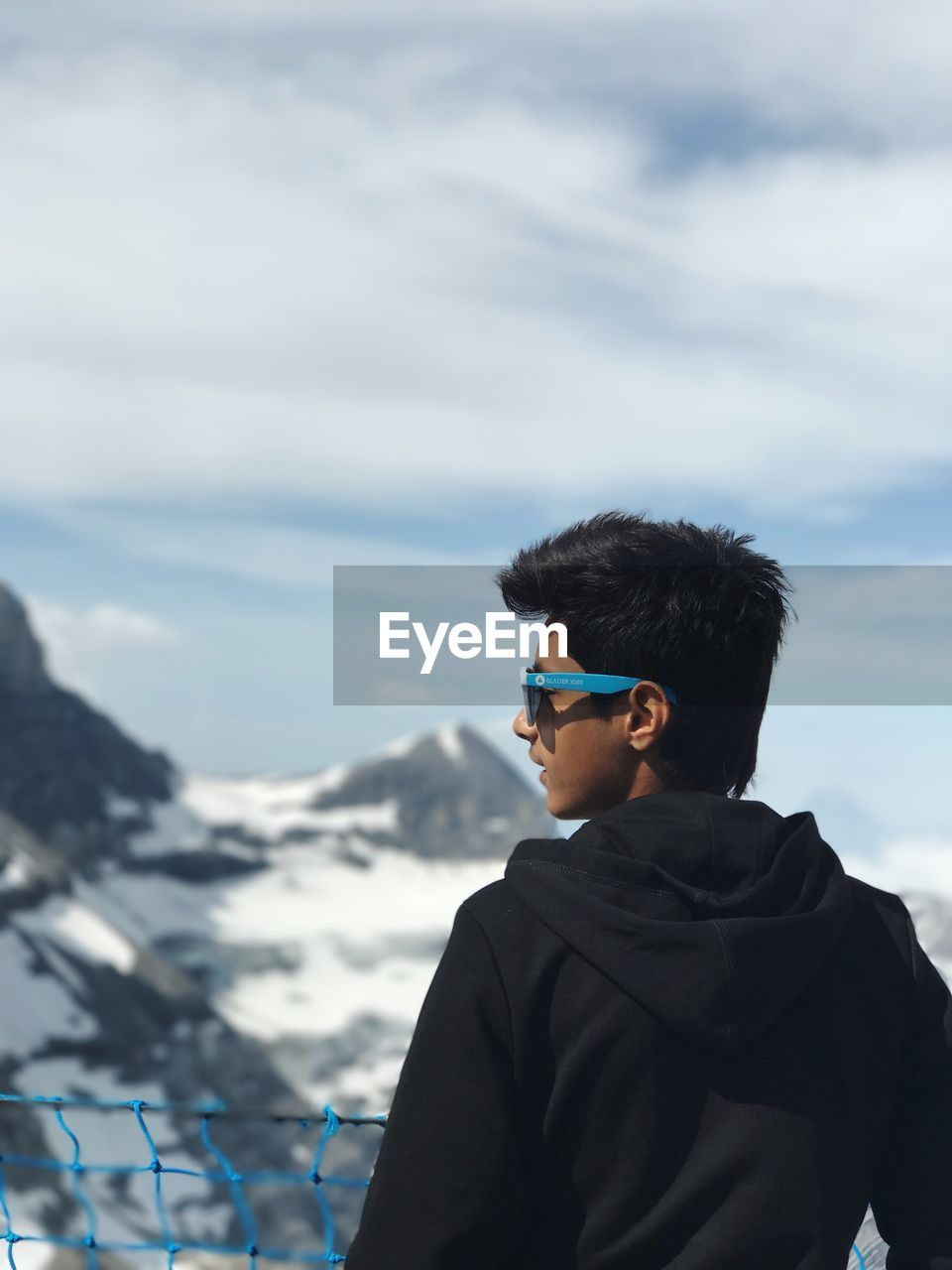 sky, real people, one person, lifestyles, leisure activity, nature, standing, cloud - sky, day, outdoors, headshot, mountain, beauty in nature, winter, water, scenics, men, young adult, people