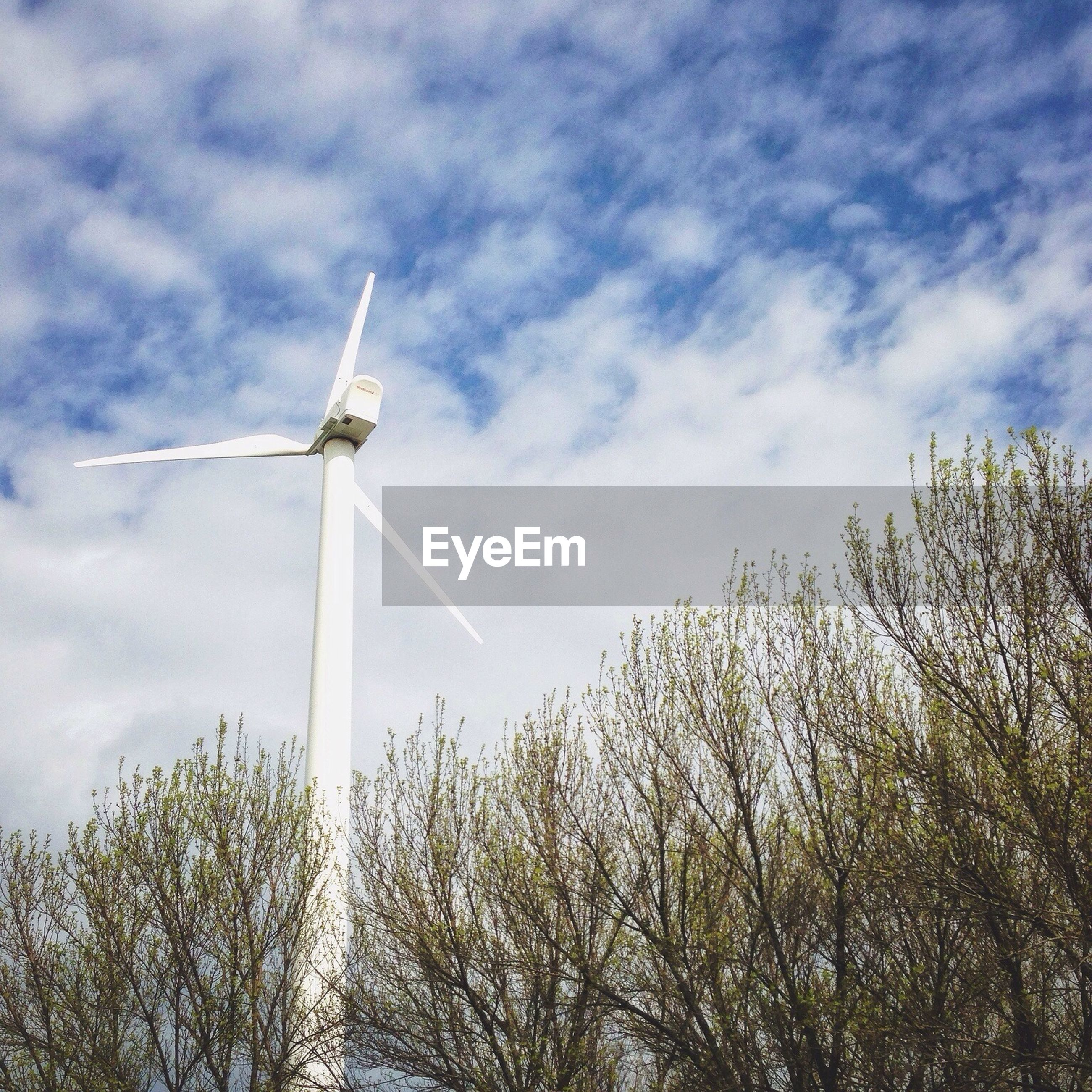 Low angle view of wind turbine against clouds