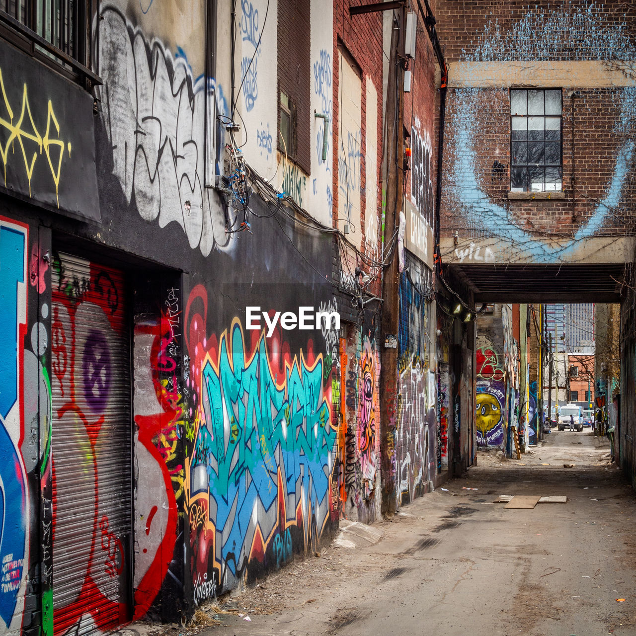 graffiti, architecture, building exterior, built structure, creativity, multi colored, art and craft, building, street art, city, wall - building feature, no people, day, street, outdoors, text, residential district, wall, alley, mural