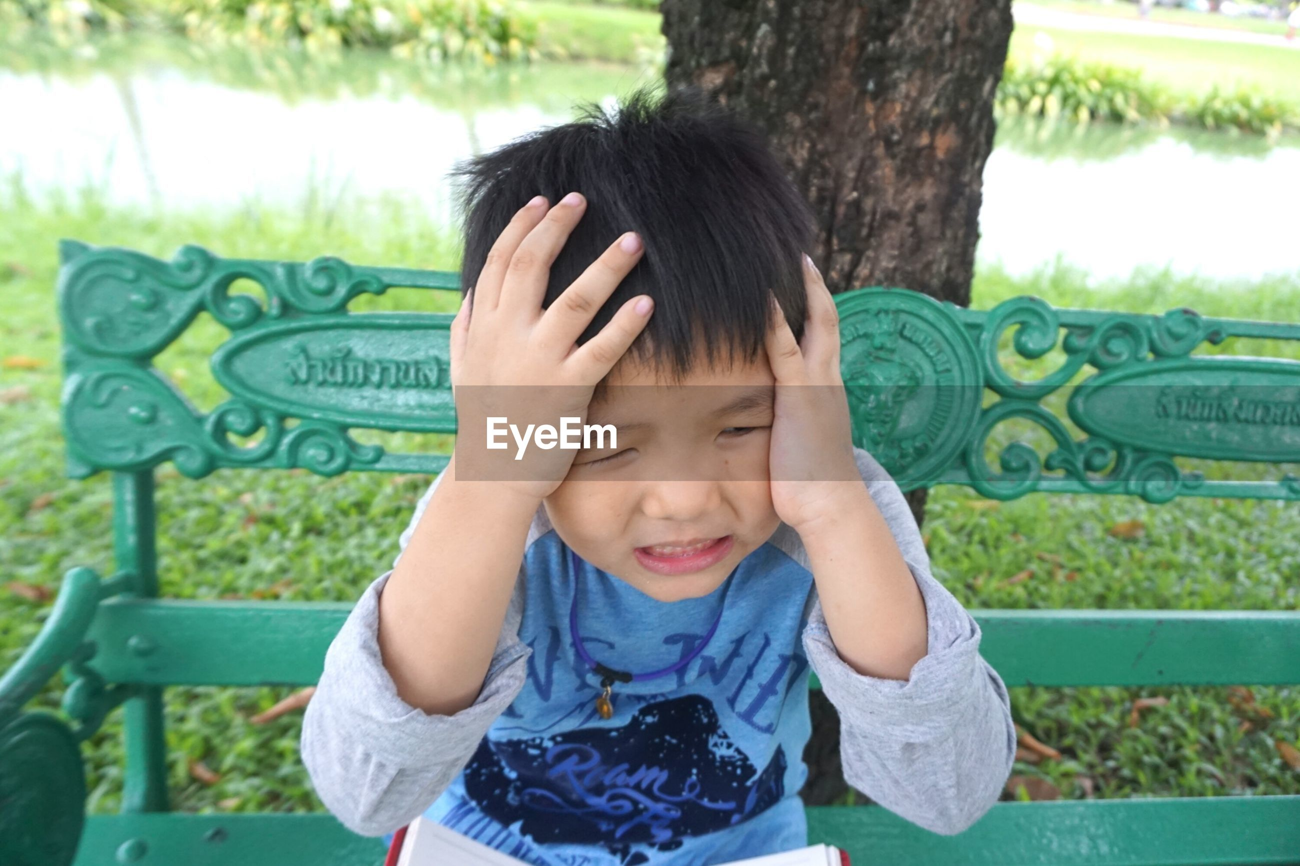 Cute boy holding his head while sitting on bench at park
