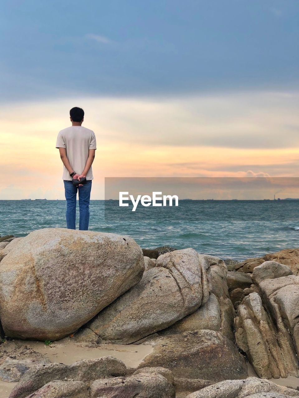 sea, rock, sky, rock - object, one person, water, rear view, standing, solid, real people, scenics - nature, beauty in nature, horizon over water, horizon, full length, leisure activity, men, cloud - sky, lifestyles, outdoors, looking at view