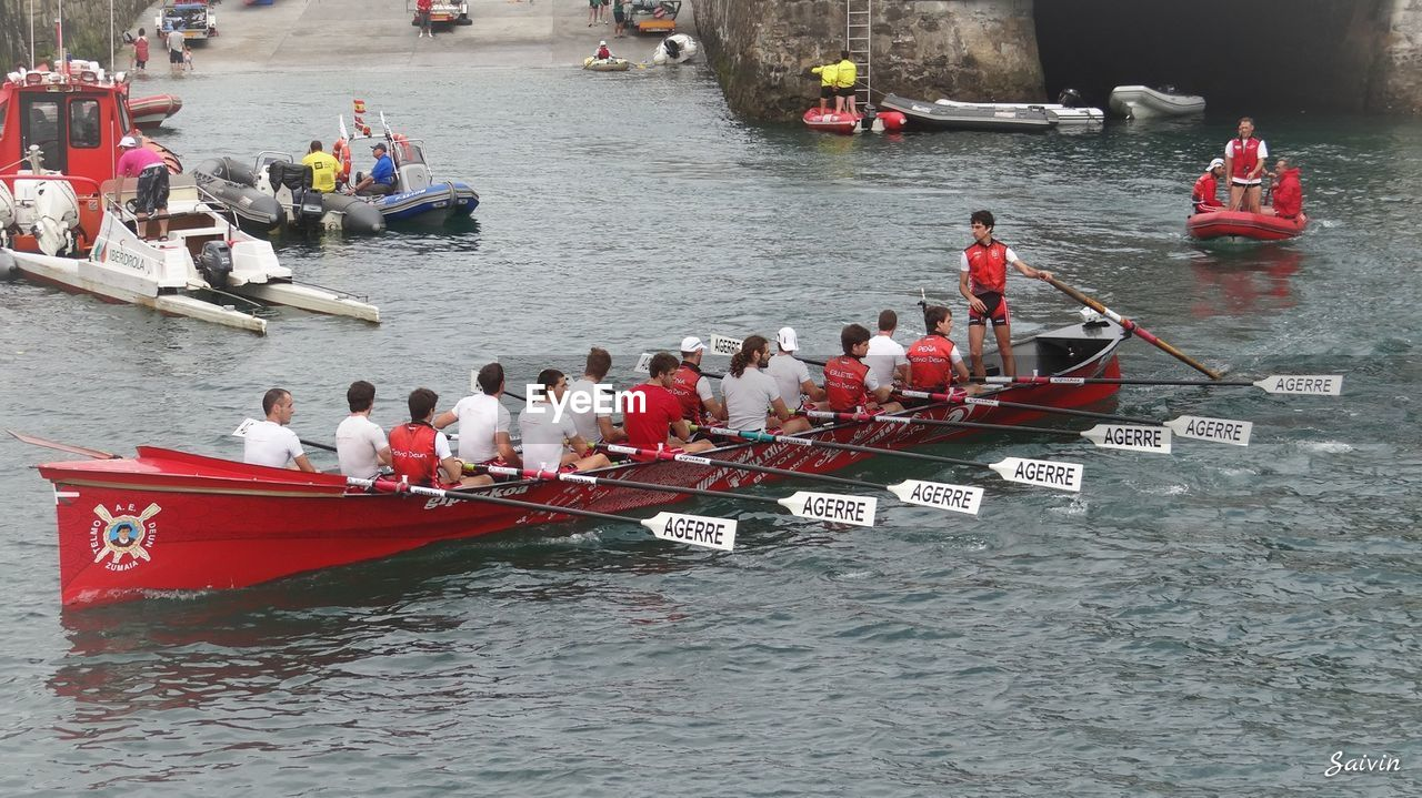 large group of people, nautical vessel, transportation, women, real people, men, mode of transport, boat, day, water, river, leisure activity, high angle view, outdoors, lifestyles, togetherness, teamwork, sitting, standing, rowing, sports race, sailing, competition, oar, adult, people