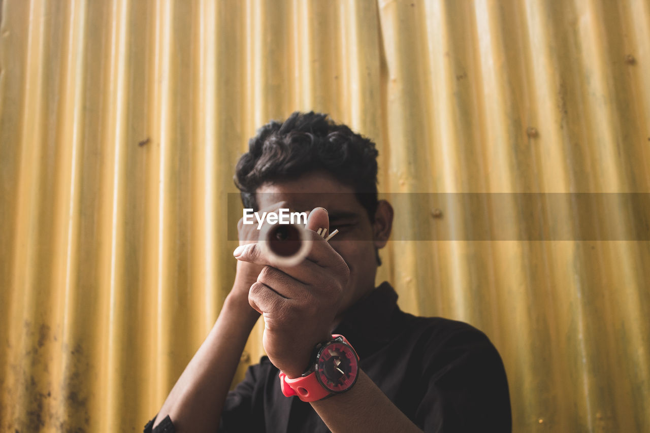 Portrait of teenage boy looking through pipe against corrugated iron