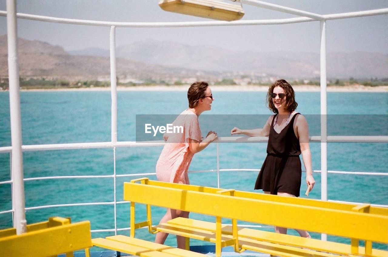 two people, water, togetherness, nature, emotion, young adult, men, sea, real people, lifestyles, leisure activity, young women, adult, women, sunlight, nautical vessel, smiling, young men, couple - relationship, positive emotion, outdoors