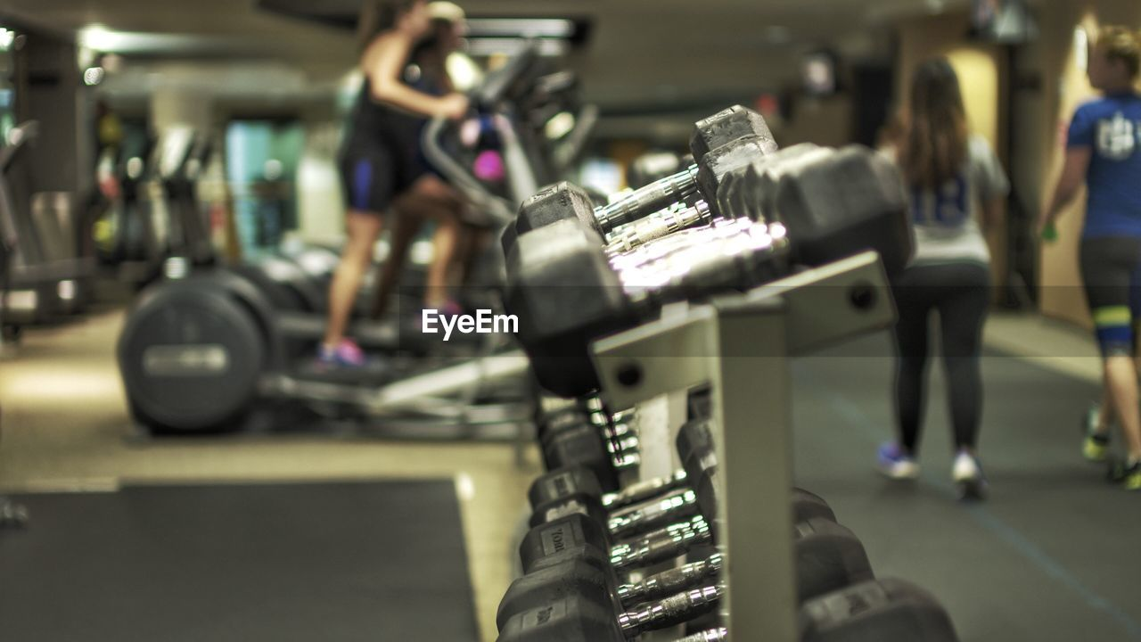 Dumbbells On Rack With People In Background At Gym
