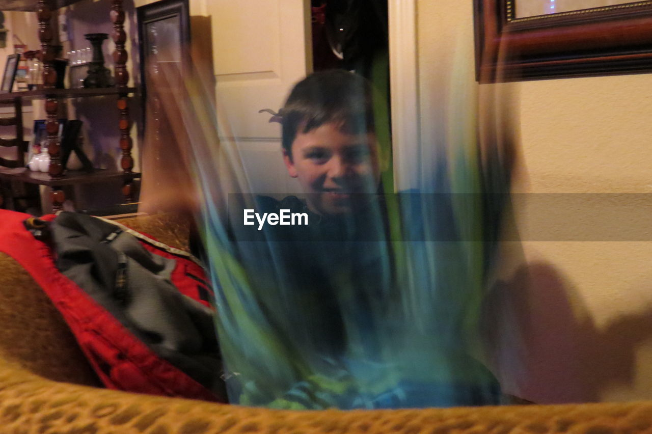 Blurred motion of boy sitting on sofa at home