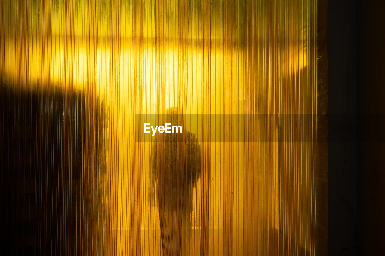 Yellow industrial plastic curtain entrance with shadow of worker and cardboard box in warehouse
