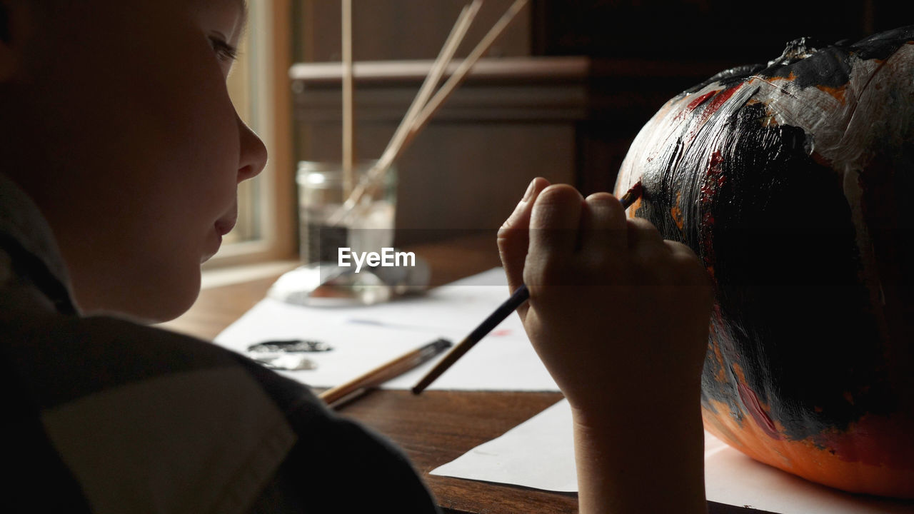 Close-up of boy painting jack o lantern at home