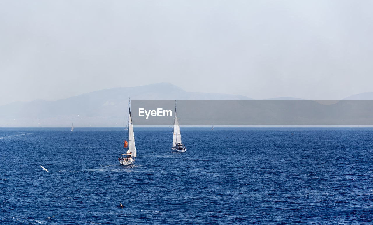 water, sea, nautical vessel, sailboat, sky, waterfront, transportation, mountain, beauty in nature, mode of transportation, scenics - nature, sailing, nature, day, tranquil scene, non-urban scene, no people, tranquility, travel, horizon over water, outdoors, yachting, yacht, luxury