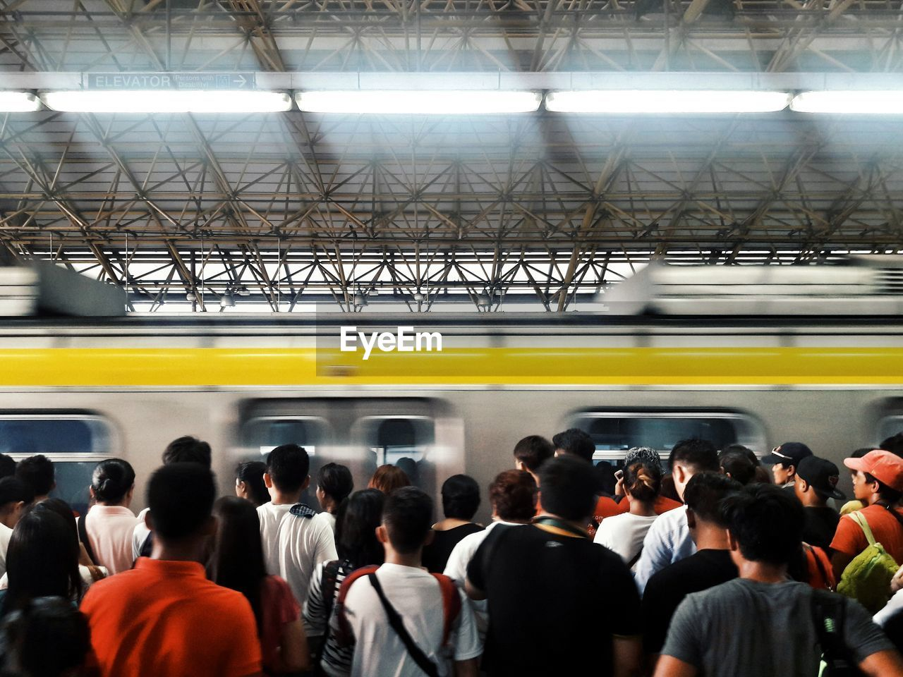 crowd, group of people, large group of people, rail transportation, transportation, public transportation, train, men, mode of transportation, real people, train - vehicle, architecture, railroad station platform, travel, motion, blurred motion, women, indoors, subway train, waiting, ceiling