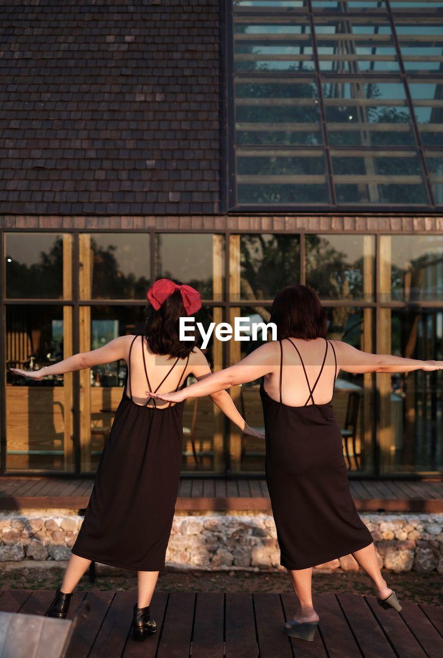 Portrait of 2 women in black backless dress against building