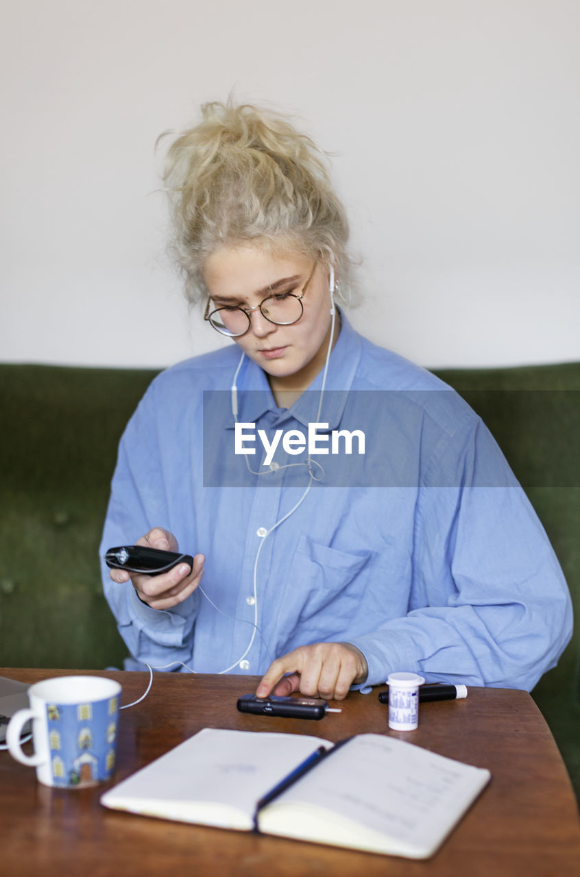 MID ADULT WOMAN USING PHONE ON TABLE