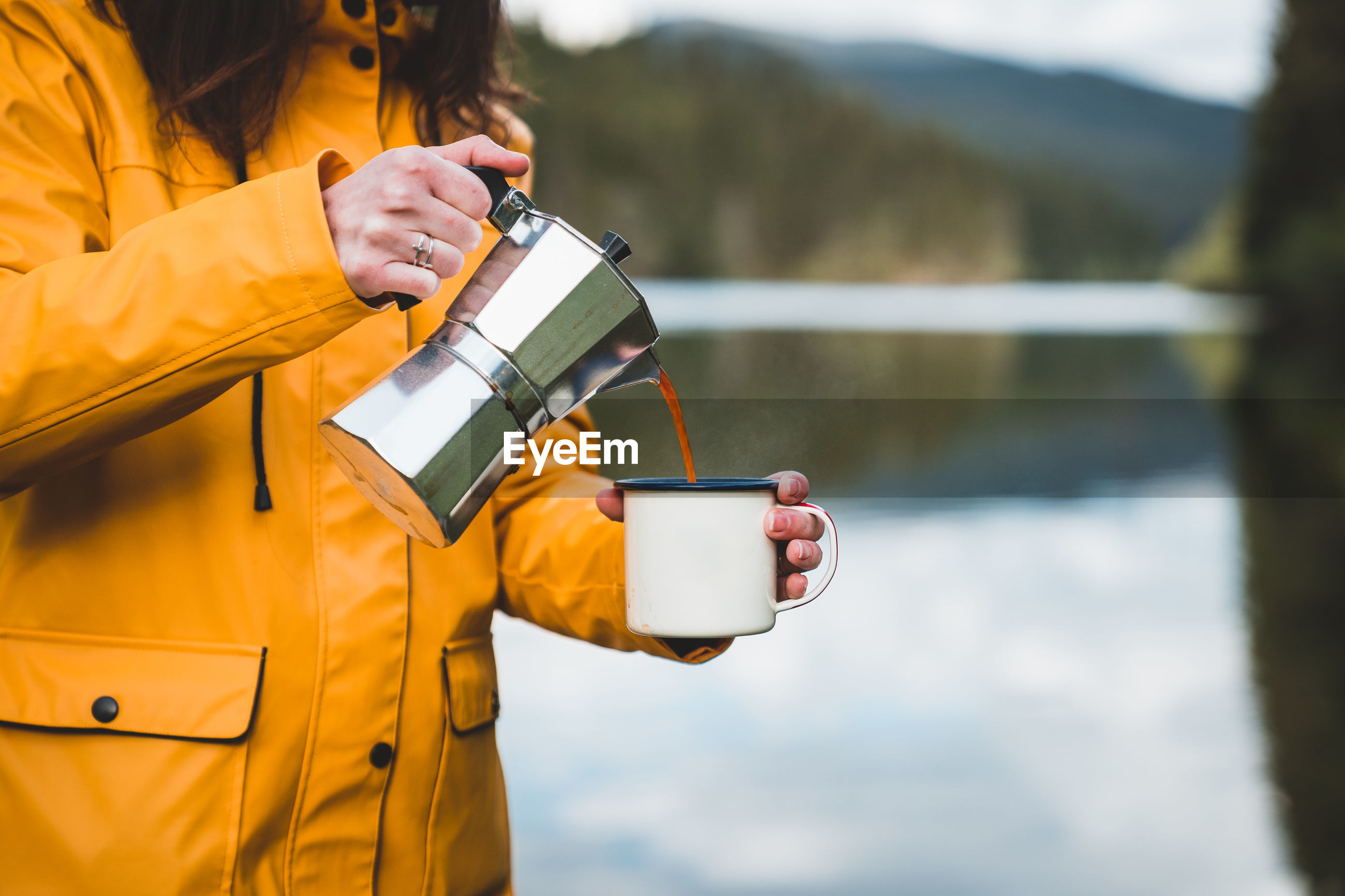 Hipster woman wearing yellow jacket pours coffee into outdoor mug from a geyser coffee maker