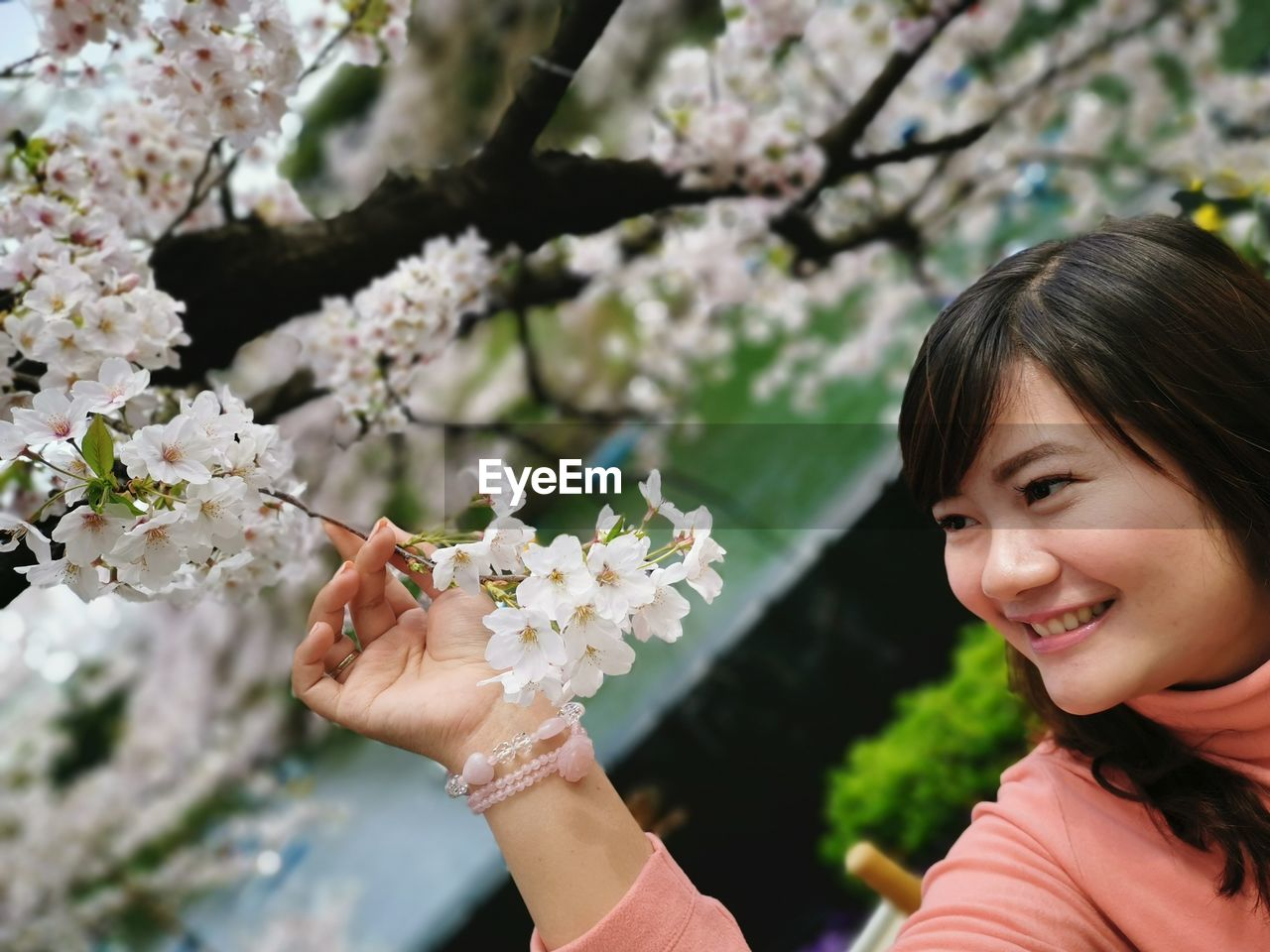 Smiling young woman looking at white flowers