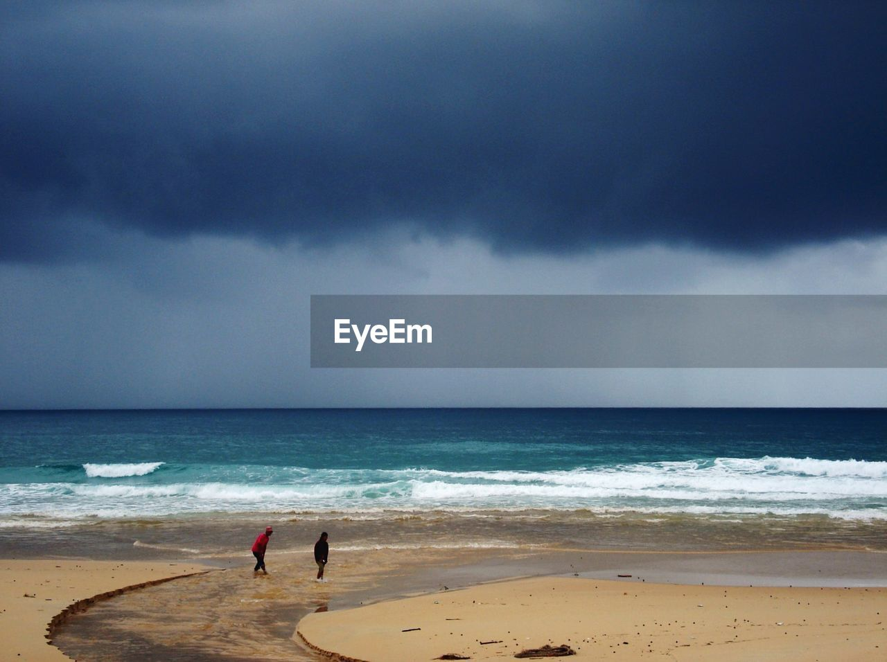 Man And Woman Standing At Beach Against Cloudy Sky