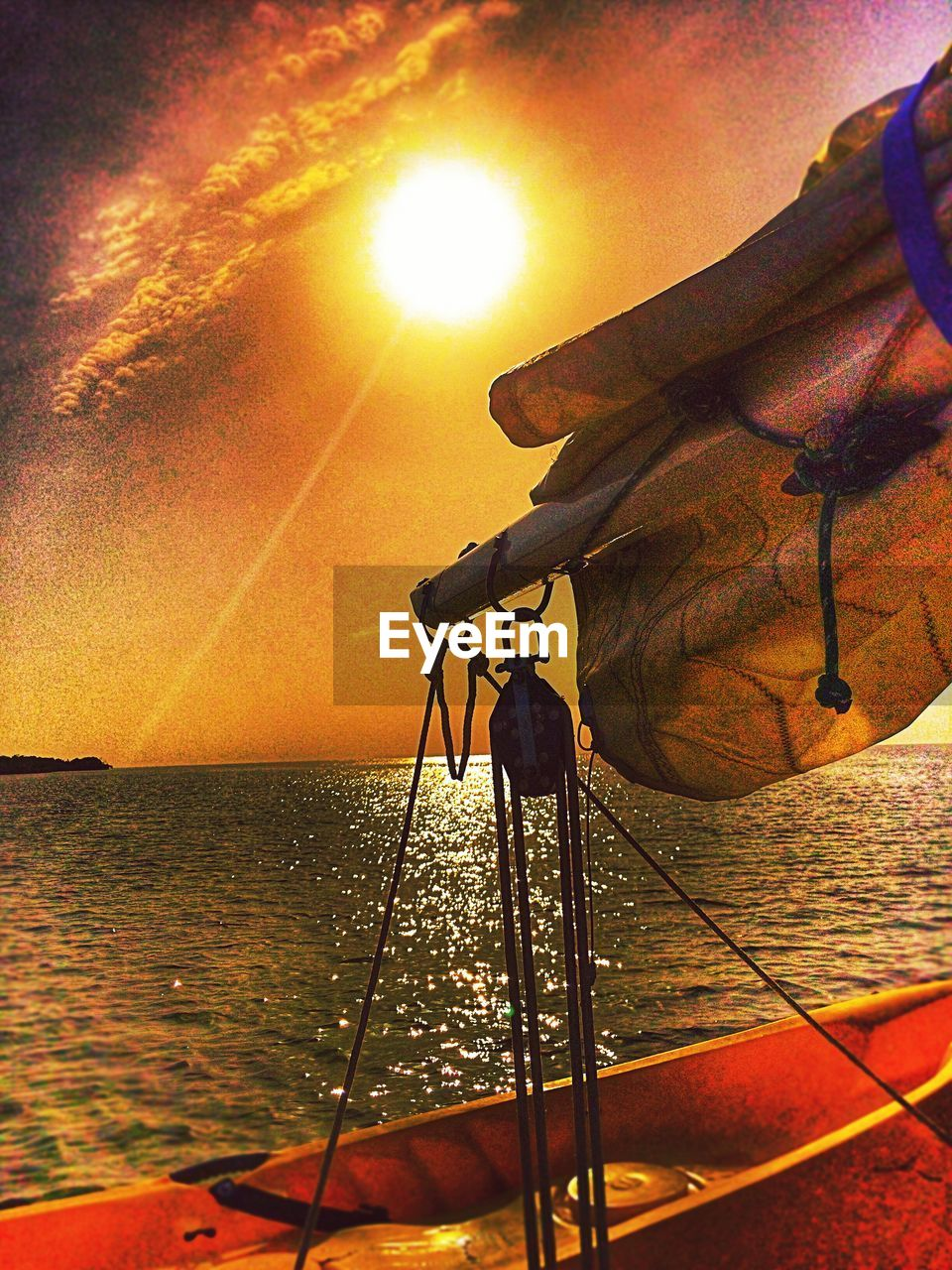 sea, sunset, water, sun, nature, sunlight, orange color, beauty in nature, outdoors, sunbeam, sky, scenics, tranquility, one person, fishing pole, horizon over water, day, nautical vessel, close-up, people