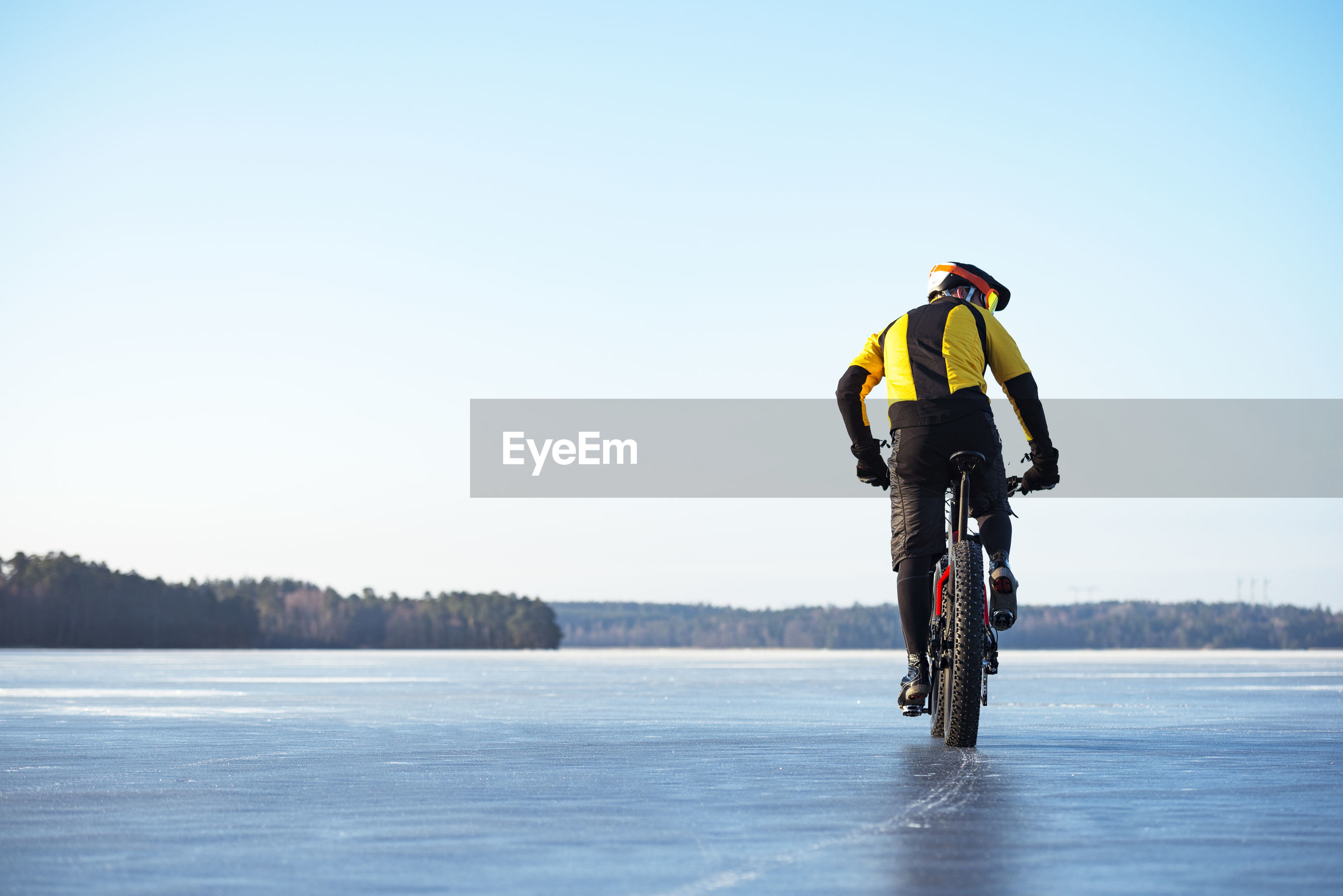 MAN RIDING BICYCLE ON SNOWY FIELD